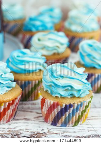 Children's cupcakes with cream cap blue on white wooden background
