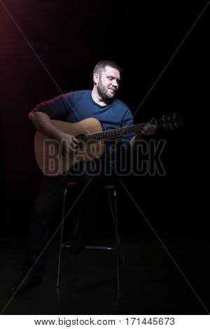 Portrait of handsome bearded man on a chair with an acoustic guitar in hand, isolated on a black background