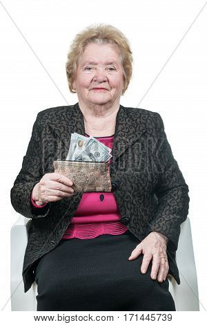 Old woman sitting on a chair holding a purse with dollars isolated on white background