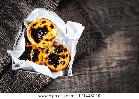 Pastel de Nata - creamy egg tart with sweet curstard black crust and sugar powder on wooden background. Pasteis de Belem pastry