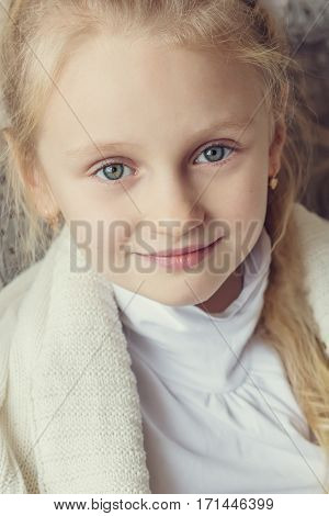 portrait of a little cute girl wrapped in a blanket