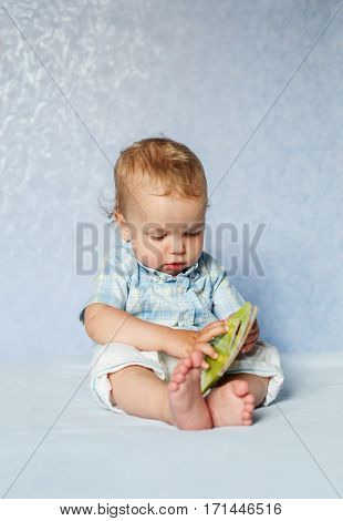 cute baby studying the book sitting on a blue background