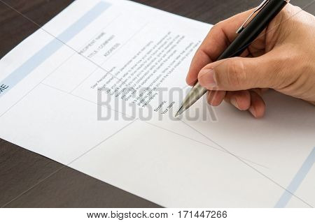 Close-up Man Signing On Resume Form.