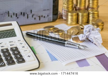Metal coins and calculator on a rustic table. The concept of a home workplace. Family budget. Planning costs and revenues.