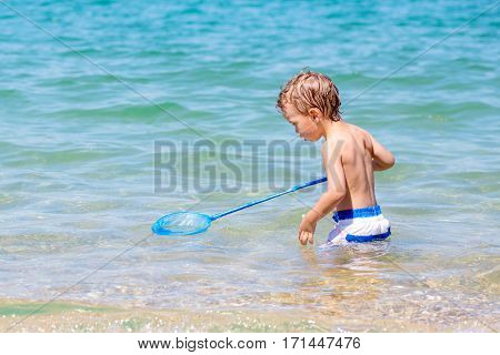 little boy fishing with a net in the sea