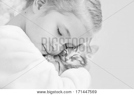 cute little girl holding a kitten on a ginger hand on a white background (black and white)