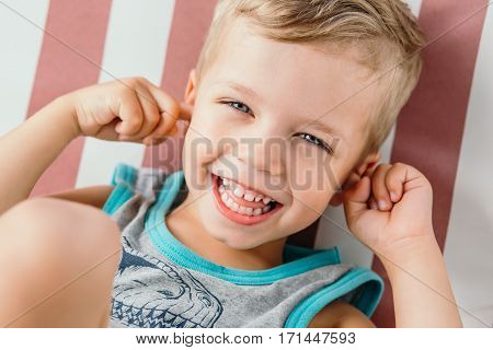 happy little boy covering his ears and laughing