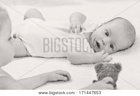 cute baby brother playing toys with sister on a white background ( black and white )