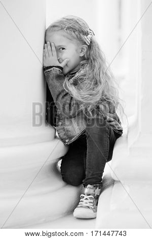 Happy little girl playing peekaboo on a white background ( black and white )