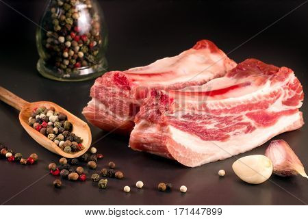 piece of pork on a dark background with peppercorn and garlic.