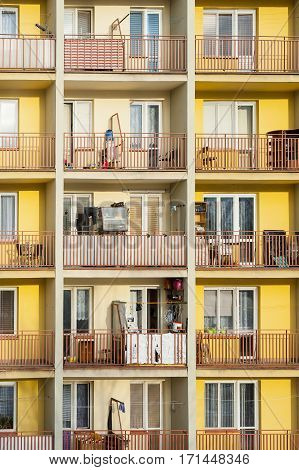 Visibly used and personalized loggias of apartment building in sunny afternoon.