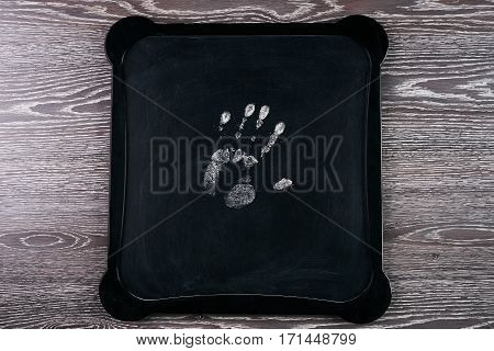 Handprint on chalkboard on wooden table .