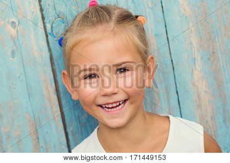 emotional portrait of a happy little girl on a blue background