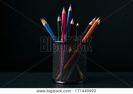 Colorful crayons pencils in black pencil box against dark background