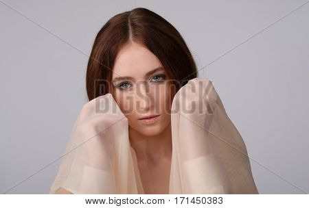 She looking, bowing her head, scarf wrapped around her shoulders. Her hands near face. Emotion: tenderness, dreaminess, lovely