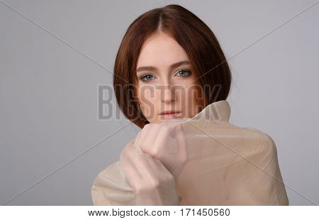 She holds in arms the part of scarf front of face. Texture of material. Make-up, fashion, tenderness
