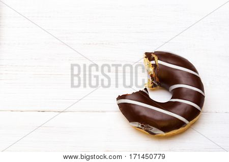 Tasty bitten donuts with icing and chocolate on white wooden background copy space