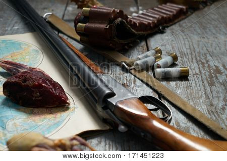 Hunting equipment on old wooden background .