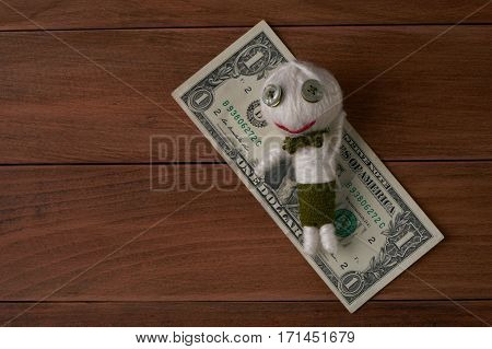 Cute Little Voodoo Doll with money on wooden background.Top view