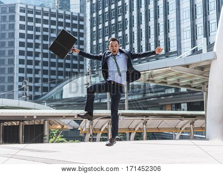 Celebrating success. Happy excited young Asian businessman jumping on the ground while holding briefcase with city in background