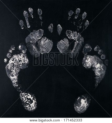 White footprint and handprint. Imprint of human foot monochrome print palm on chalkboard.Top view.