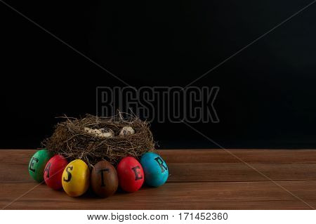 Easter holidays tradition and object concept - of colored easter eggs and quaill eggs in nest on wooden surface.black background.Copy space.