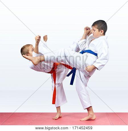 Friends in karategi beat kick towards each other