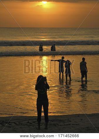 at Kuta People having fun at sunset on Kuta beach, warm colors.