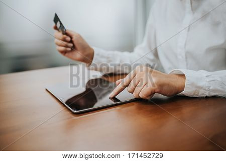 Woman hand using tablet and credit card for shopping online. Fintech concept.