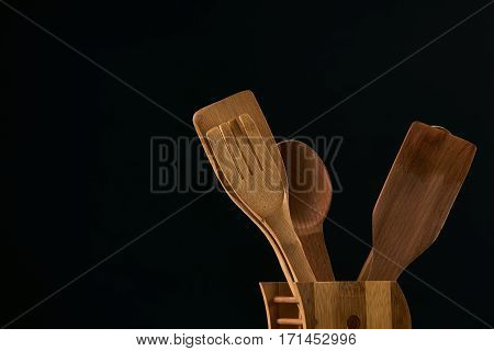 Set of the wooden kitchen utensils on black background. spoon kitchen spatula rolling pin fork closeup copy space.