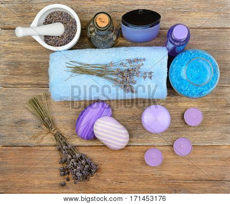 Goods for spa: soap, sea salt, towel, oil of lavender on wooden table. top view