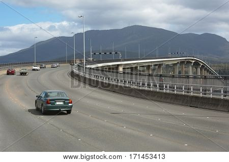 Highway bridge with cars passing by, driving on the left in Tasmania
