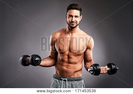 A half naked handsome young sportsman lifting a dumbbells with both hands