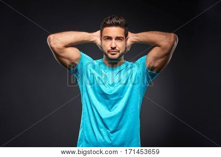 A handsome young sportsman standing confidently with his arms above his head