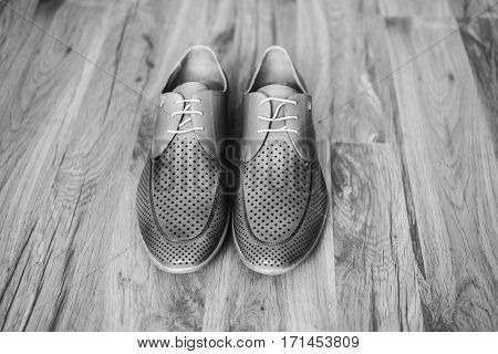 Black and white art photography monochrome gray man's shoes on the floor. Men's style fashion. Charges groom.