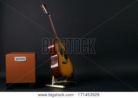 Combo amplifier for guitar with classical acoustic guitar on the black background with copy space