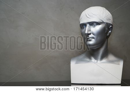 White plaster bust sculpture portrait of a young man on an decorative background.