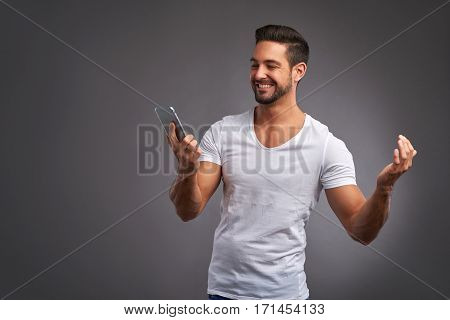 A handsome young man holding his phone and celebrating