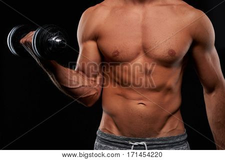 Closeup look of half naked handsome young sportsman upper body while lifting a dumbbell with one hand