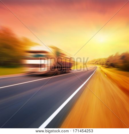 Motion blurred truck on blurry asphalt road at sunset.