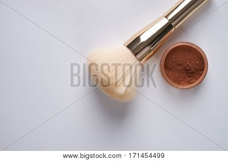 Face powder and brush isolated on white background top view with copy space.