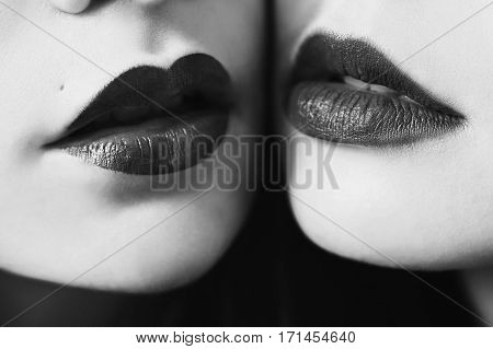 Black and white art photography monochrome female lips with bkack lipstick matte closeup. Macro photo. Girls lesbians