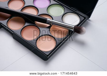 Make up professional cosmetics palette with eyeshadow and brush on it isolated on white. Professional make-up tools closed-up.