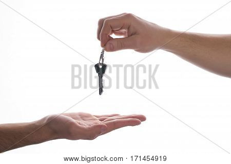 One hand giving key to another on isolated white background. Process of buying renting selling. Agreement between two people about sales purchase.