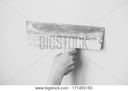 Black and white art photography monochrome working tool spatula in hand on a light background work plasterer painter to make repairs