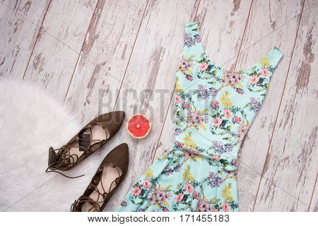 Bright summer dress brown suede shoes on a white fur grapefruit. Wooden background. Fashionable concept top view