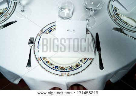 Beautiful banquet table with plates cutlery and greeting card for christening served for VIP. Holiday wedding celebration concept.