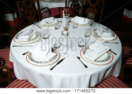 Beautiful banquet table with plates cutlery and greeting card for christening served in cozy home style for VIP. Holiday wedding celebration concept.