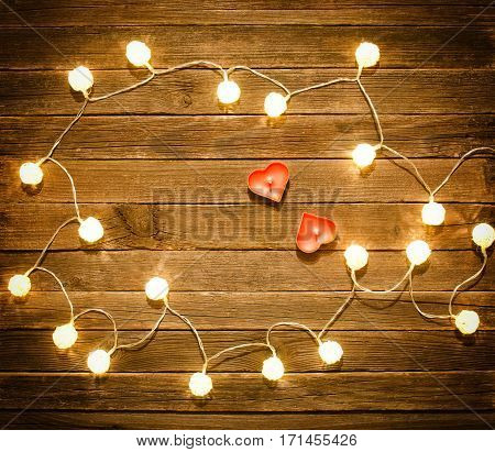 Two candles in the shape of heart among the glowing lanterns made of rattan on a wooden background. View from above space for text