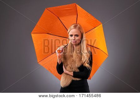 A beautiful young woman feeling sad and holding an umbrella wearing a stole